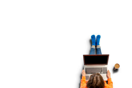Young woman holding a laptop on his knees, standing next to a cup of coffee. Top view, flat lay.