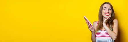 Smiling cute young girl holding a phone and holding her hand under her chin on a yellow background. Banner