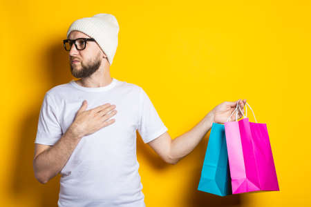Young man with beard looks to the side and holds shopping bags on yellow background 免版税图像