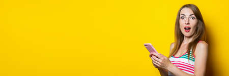 Surprised shocked young woman in a striped dress holds a phone in her hands on a yellow background. Banner
