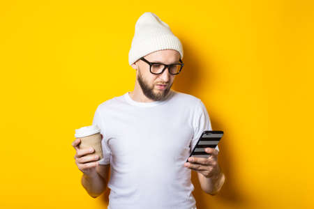 Bearded young guy with cardboard glass with coffee looks into the phone on a yellow background