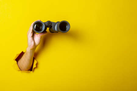 Female hand holds black binoculars on a yellow background. Looking through binoculars, journey, find and search concept.