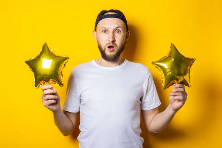 Surprised shocked bearded young man holding air balloons golden in the form of a star on a yellow background
