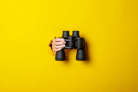 Female hand holds black binoculars on a yellow background. Journey, find and search concept. 免版税图像