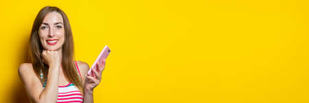 Smiling young girl holding a phone and holding her hand under her chin on a yellow background. Banner