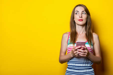 Serious young girl with a phone looks to the side on a yellow background.
