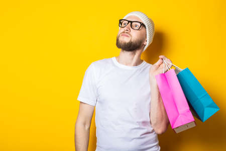 Bearded young man looking up and holding shopping bags on yellow background