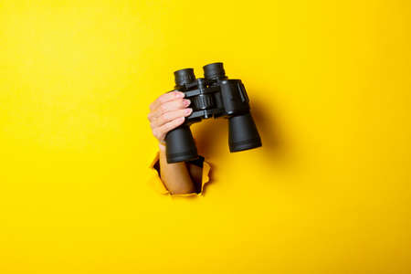 Female hand holds black binoculars on yellow background, travel, find and search concept.