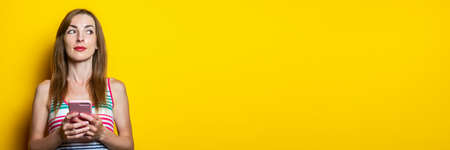 Serious young girl with a phone looks to the side on a yellow background. Banner
