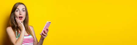 Surprised young woman in a striped dress holds a phone in her hands on a yellow background. Banner 免版税图像