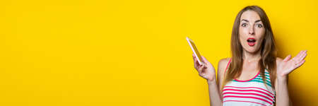 Shocked surprised young woman holds a phone in her hand on a yellow background. Banner 免版税图像