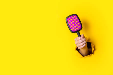 Female hand holds a large black with pink hairbrush on a yellow background 免版税图像
