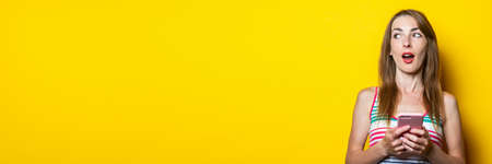 Surprised young woman with phone looks side over yellow background. Banner