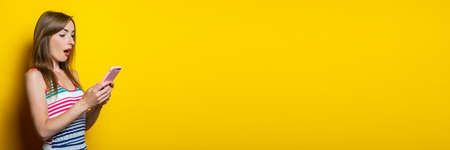 Surprised shocked young girl in a striped dress holds a telephone on a yellow background. Banner 免版税图像