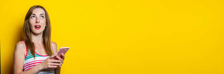 Serious young girl with a phone looks up on a yellow background. Banner