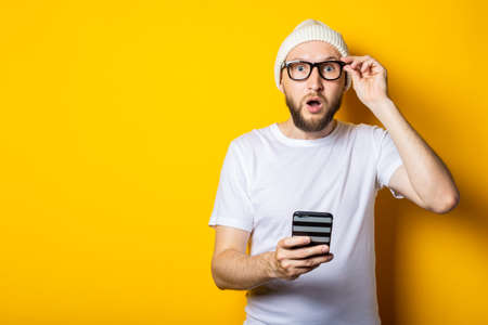 Bearded young man in shock surprised looks at the phone on a yellow background.