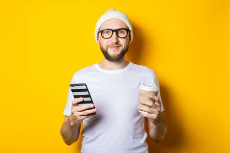 Smiling bearded young man holding phone and cardboard glass with coffee on yellow background