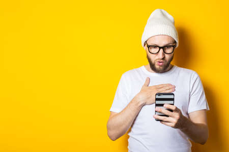 Surprised young man with a beard looks at the phone on a yellow background.