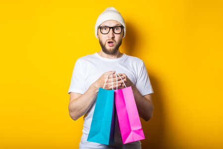 Bearded surprised shocked young man in glasses holds two bags of purchases on yellow background