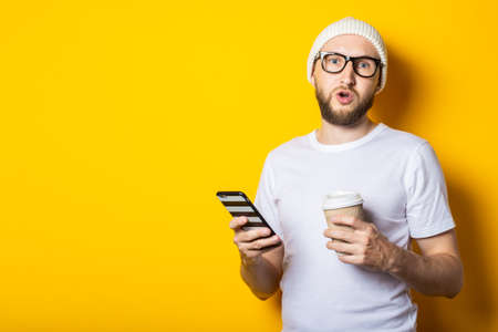 Surprised shocked bearded young man holding a phone and a cardboard glass with coffee on a yellow background.