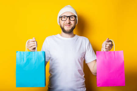 Friendly smiling bearded young man in glasses and a hat holding packages with purchases on a yellow background 免版税图像