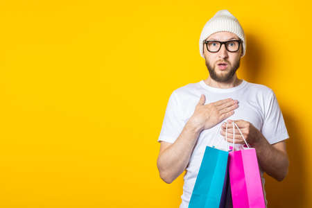 Bearded surprised young man in glasses and a hat holding shopping bags on yellow background 免版税图像