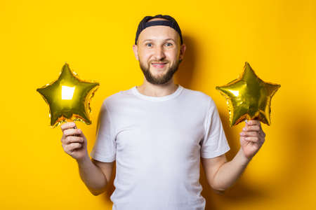 Smiling bearded young man holding air balloons golden in the form of a star on a yellow background
