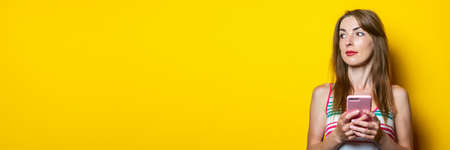 Pensive cute young woman with the phone looks up on a yellow background. Banner