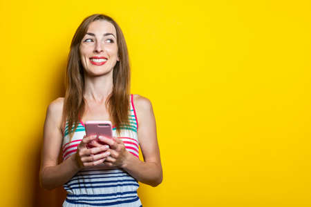 Cute young woman with phone smiling looks aside on a yellow background. Banner