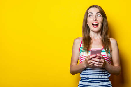Happy pretty young woman with phone looks side on yellow background. 免版税图像