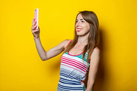 Young woman holding a phone communicates by video chat on a yellow background