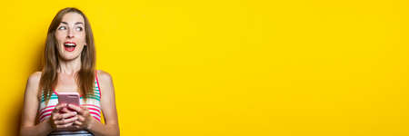 Happy pretty young woman with phone looks side on yellow background. Banner 免版税图像