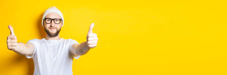 Smiling affable young guy with a beard in a cap and glasses shows a gesture with his hands, thumbs up, class on a yellow background. Banner