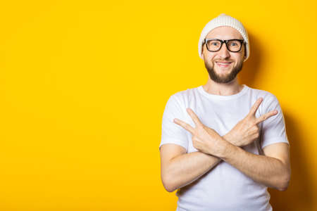 Young guy with a beard in a hat and glasses shows gestures with his hands, arms crossed and two fingers up
