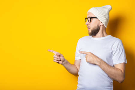 Surprised young guy with a beard in a hat and glasses points his fingers to the side on a yellow background Stock Photo