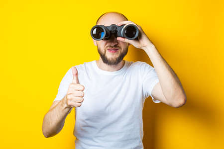 Smiling bald young man with a beard looks through binoculars and shows a thumb up on a yellow background.
