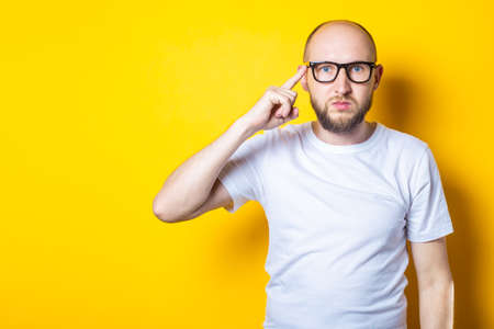 Serious bearded bald young guy in glasses holds a finger to his temple on a yellow background