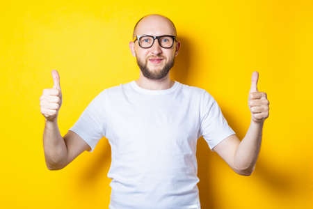 Smiling bearded bald young man showing gesture with hands, thumbs up, class on yellow background