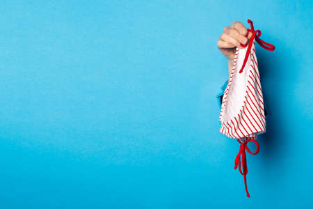 Woman's hand on a blue background holds white panties with red stripes
