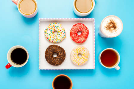 Tasty donuts and cups with hot drinks, coffee, cappuccino, tea on a blue background. Concept of sweets, bakery, pastries, coffee shop, meeting, friends, friendly team. Flat lay, top view. Foto de archivo