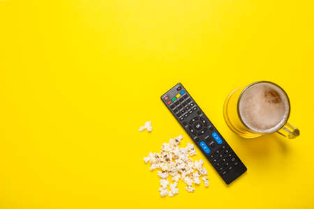 Remote control from a TV or TV tuner, a glass of beer and popcorn on a yellow background. Concept series, film, sports. Banner. Flat lay, top view.