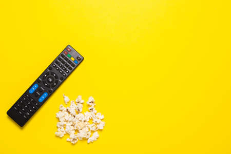 TV remote control, TV tuner or audio system and popcorn on a yellow background. Concept series, film, sports. Banner. Flat lay, top view.