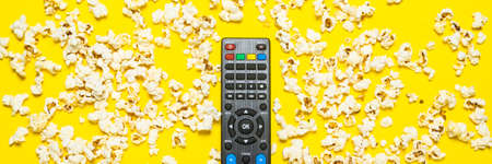 Black remote control from a TV, TV tuner or audio system on a yellow background with popcorn. Concept TV series, film, sports. Flat lay, top view.