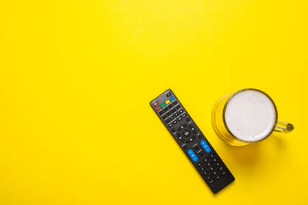 Remote control from the TV or TV tuner, a glass of beer on a yellow background. Concept series, film, sports. Banner. Flat lay, top view.