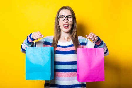 Young woman in sweater holds shopping bags with purchases on yellow background.