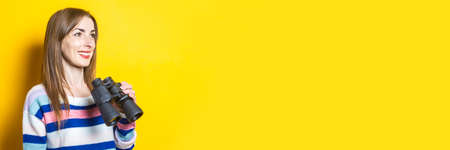 Young woman looks into the phone and holds shopping bags with purchases on a yellow background. Banner.