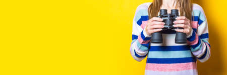 Woman holding binoculars in her hands on a yellow background. Banner.