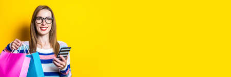 Young woman smiling and holding a phone and shopping bags with purchases on a yellow background. Banner. Reklamní fotografie