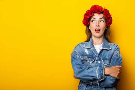 Young woman with a surprised face looks to the side in a denim jacket and a wreath of red flowers on her head on a yellow background.