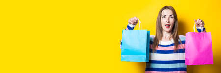 Young woman with a smile in a sweater holds shopping bags with purchases on a yellow background. Banner.